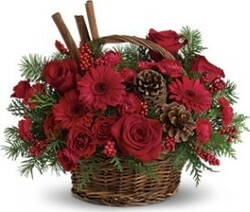 Basket of roses, gerberas and mixed flowers in warm colors for Christmas