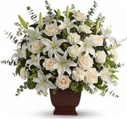 Delicate funeral arrangement of roses, lilies and mixed flowers