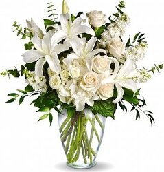 Funeral Roses, Lisianthuses, and Lilies arrangement decorated with seasonal greenery