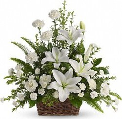 Funeral arrangement of delicate lilies, carnations and mixed flowers
