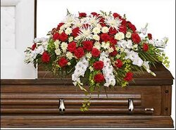 Funeral spray of red and white carnations and mixed flowers